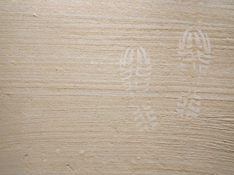 Schoenvoetafdruk op grijze het zandachtergrond van het concrete oppervlaktestof stock afbeeldingen