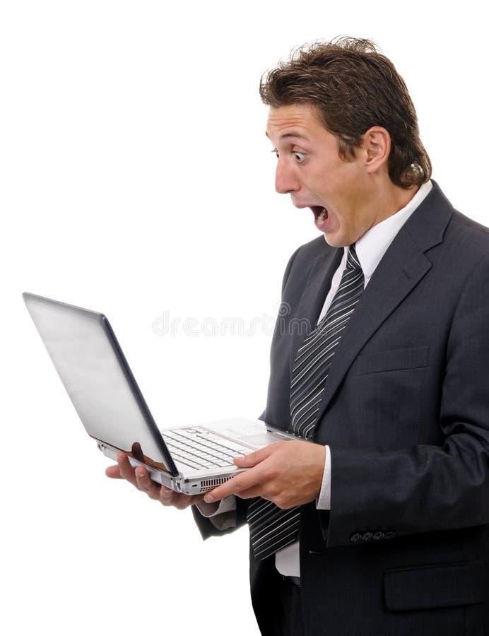 Schokierende Geschäftsmannlesemeldung auf Laptop lizenzfreies stockfoto