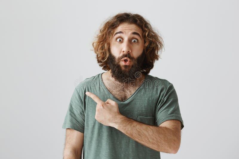 Schokinhoud achter deze hoek Binnenschot van verbaasd en overweldigd oostelijk mannetje die met baard en krullend haar kijken met stock fotografie