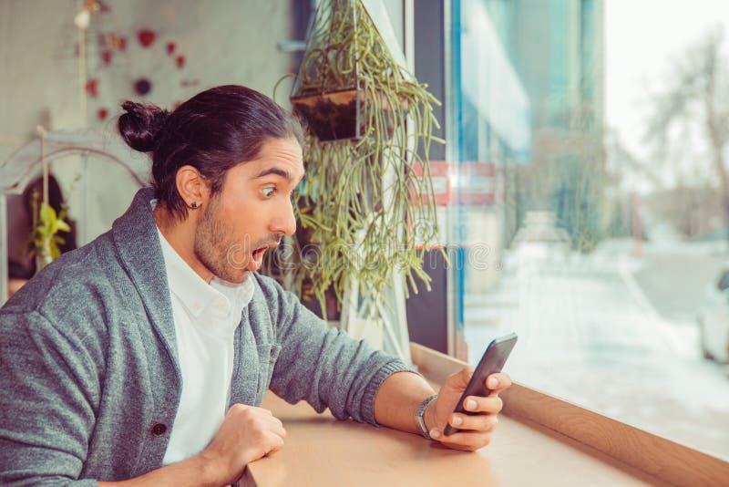 Schokkend sms, nieuws Geschokte mens die telefoon bekijken stock afbeelding
