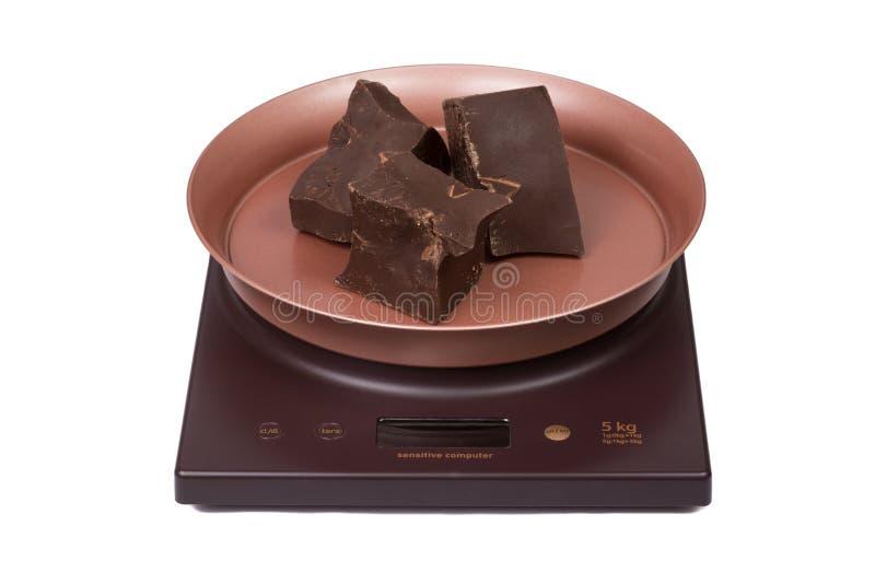 Schokolade auf den elektronischen Skalen der Küche lizenzfreie stockfotos