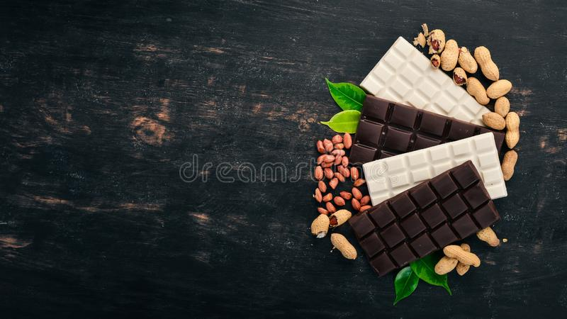 Schokolade aus dunkler und weißer Milch mit Erdnussnüssen Auf Holzboden stockfotos