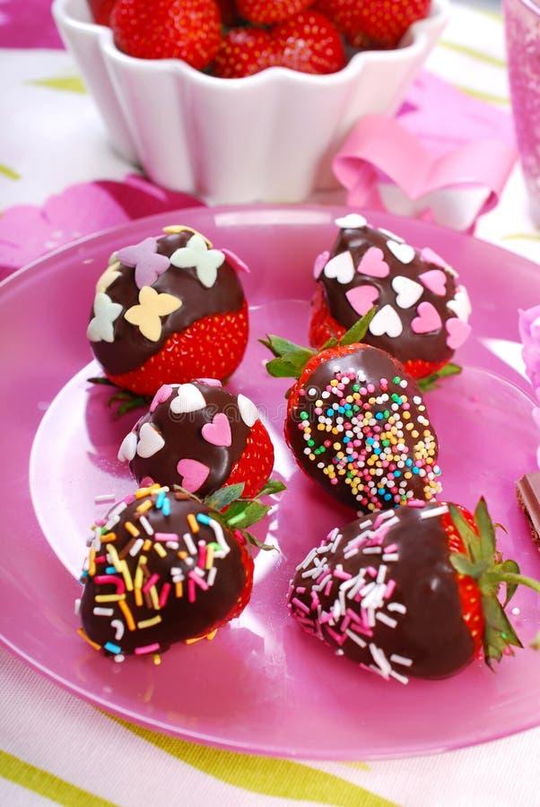 Schokolade bedeckte frische Erdbeeren mit buntem besprüht stockbild