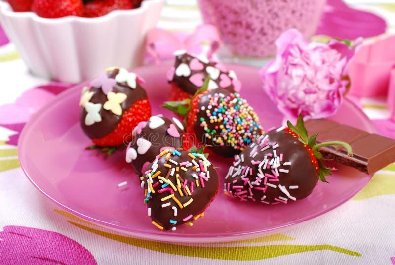 Schokolade bedeckte frische Erdbeeren mit buntem besprüht lizenzfreie stockfotos