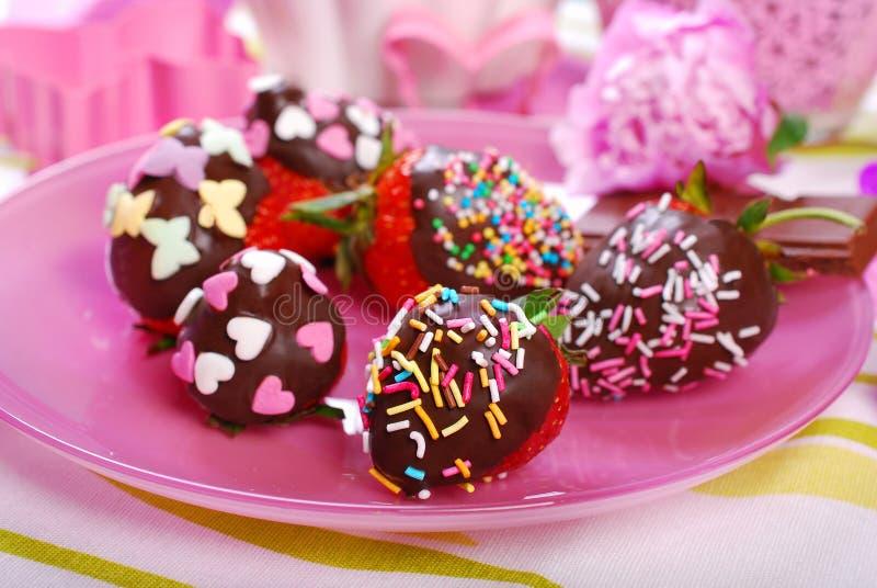 Schokolade bedeckte frische Erdbeeren mit buntem besprüht stockbilder