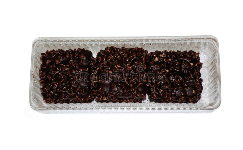 Schokolade bedeckte quadratische Plätzchen mit den Nüssen im Kunststoffgehäuse lokalisiert auf weißem Hintergrund stockfotografie