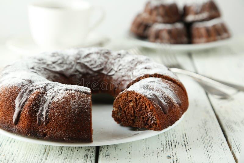 Schokolade bundt Kuchen auf Platte auf weißem hölzernem Hintergrund stockbild
