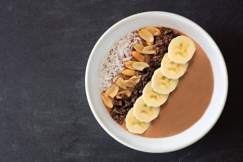 Schokolade, Erdnussbutter, Banane, Smoothieschüssel auf Schiefer lizenzfreies stockbild