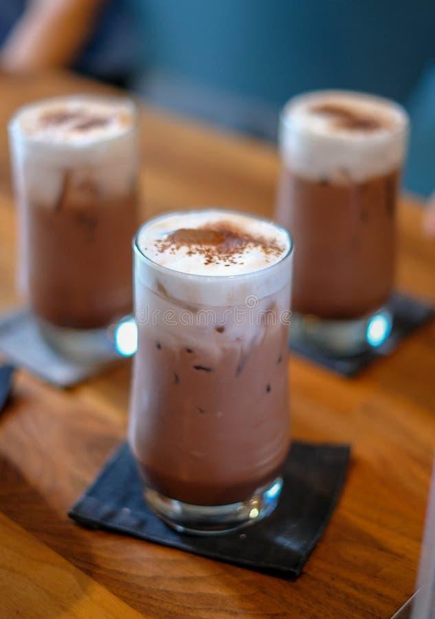 Schokolade mit Milchschaum in einem Glas, auf einen Holztisch gelegt lizenzfreies stockfoto
