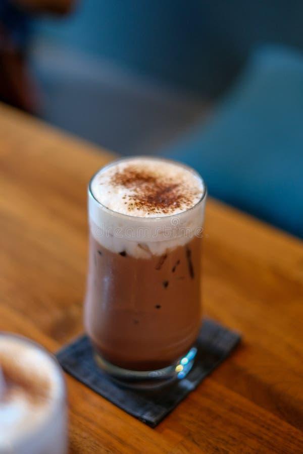 Schokolade mit Milchschaum in einem Glas, auf einen Holztisch gelegt stockfotografie