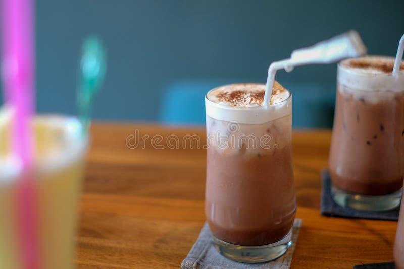 Schokolade mit Milchschaum in einem Glas, auf einen Holztisch gelegt stockfotos