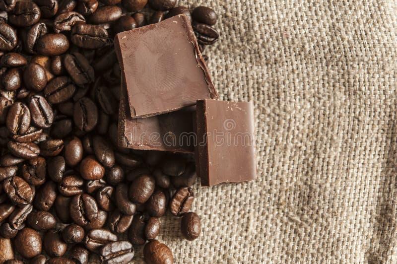 Schokolade und Kaffeebohnen auf einem Textilhintergrund lizenzfreie stockfotografie