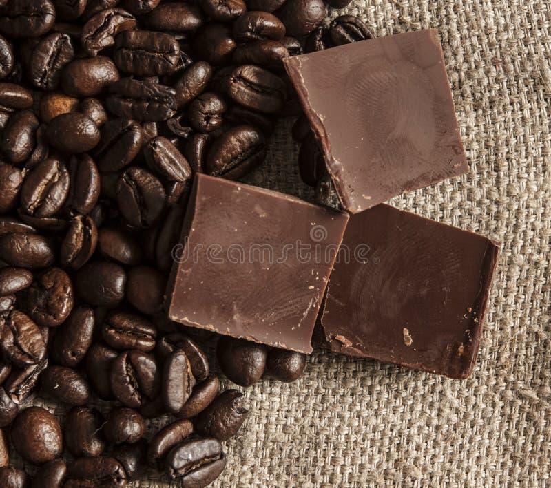 Schokolade und Kaffeebohnen auf einem Textilhintergrund lizenzfreie stockbilder