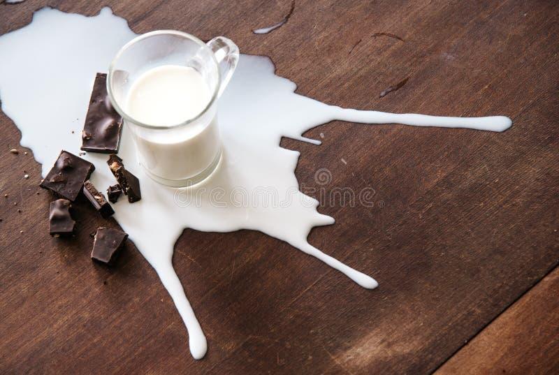 Schokolade und verschüttete Milch auf dem Tisch stockbilder