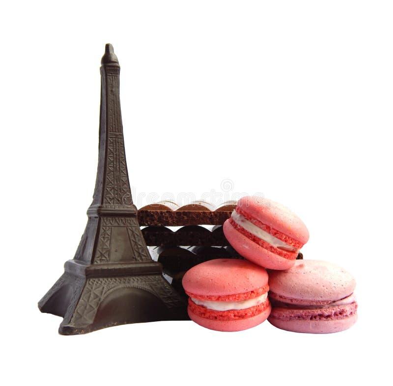 Schokoladen-Eiffelturm, drei macarons und defekte Milch- und DunkleSchokoriegel auf weißem Hintergrund stockfotos
