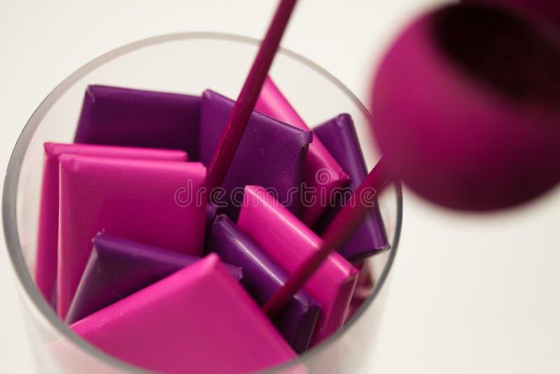 Schokoladen eingewickelt im magentaroten und purpurroten Papier stockbilder