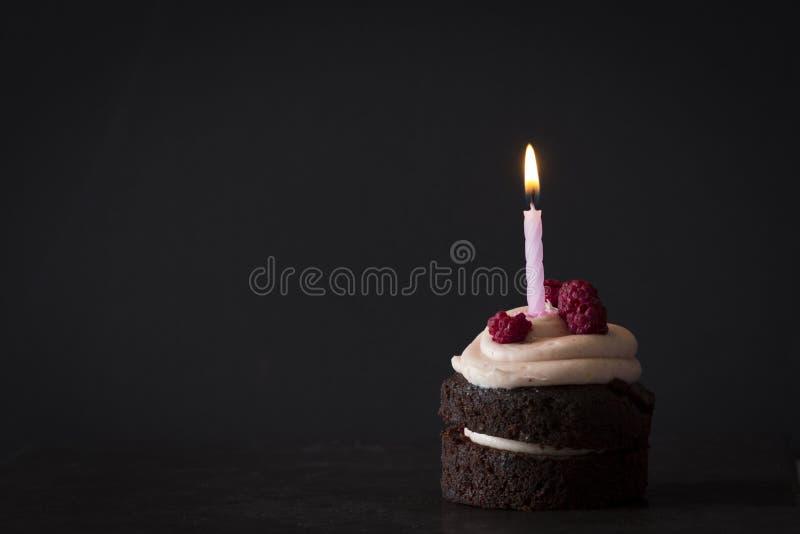Schokoladen-Geburtstags-kleiner Kuchen mit Himbeeren und Kerze stockbild