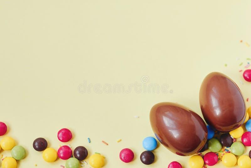 Schokoladen-Ostereier und Bonbons auf gelbem Pastellhintergrund lizenzfreie stockbilder