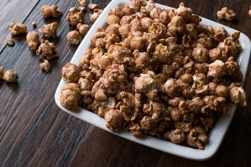 Schokoladen-Popcorn auf dunkler Holzoberfläche stockfotografie