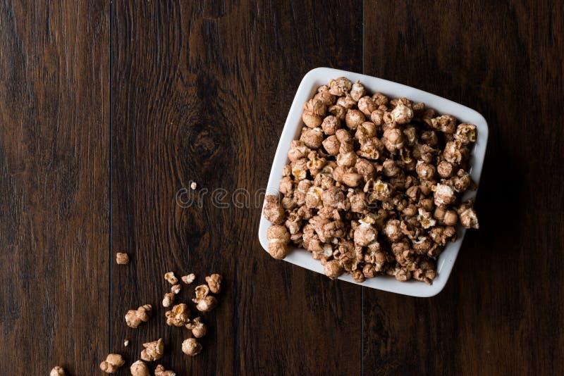 Schokoladen-Popcorn auf dunkler Holzoberfläche lizenzfreie stockfotografie