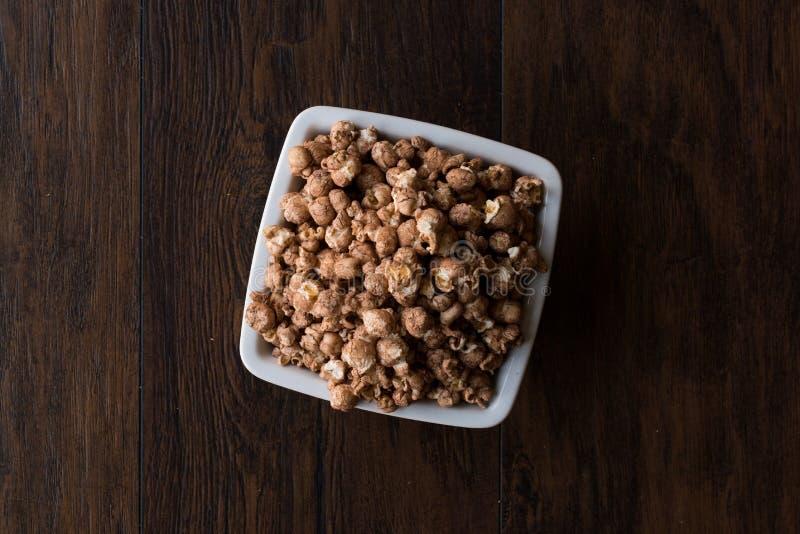 Schokoladen-Popcorn auf dunkler Holzoberfläche stockfotos
