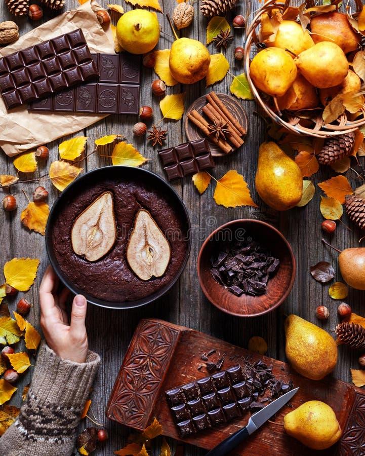 Schokoladen-Schokoladenkuchen mit einer Birne in einer Backform wird durch eine weibliche Hand in einer Strickjacke gehalten Lebe lizenzfreies stockbild