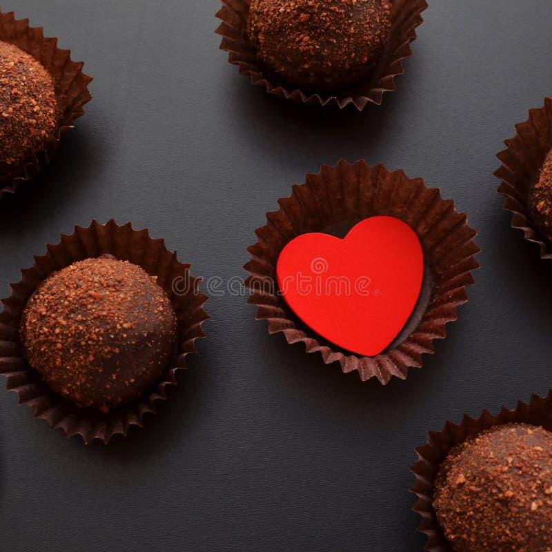 Schokoladenbonbons in der Verpackung mit rotem Herzen über schwarzem Hintergrund stockbild