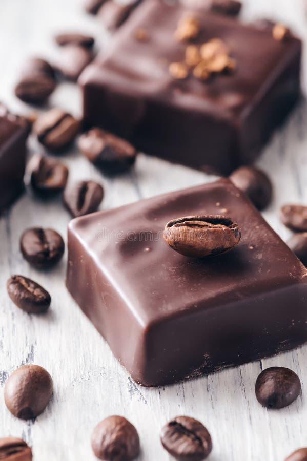 Schokoladenbonbons mit Kaffeebohnen auf einem Holztisch lizenzfreies stockbild