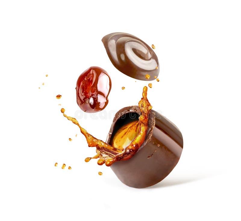 Schokoladenbonbons mit Kirschen und Kognak spritzt lokalisiert auf w lizenzfreies stockbild
