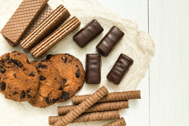 Schokoladenbonbons, Schokoladenwaffelrollen, Plätzchen auf einer hölzernen weißen Tabelle lizenzfreie stockbilder