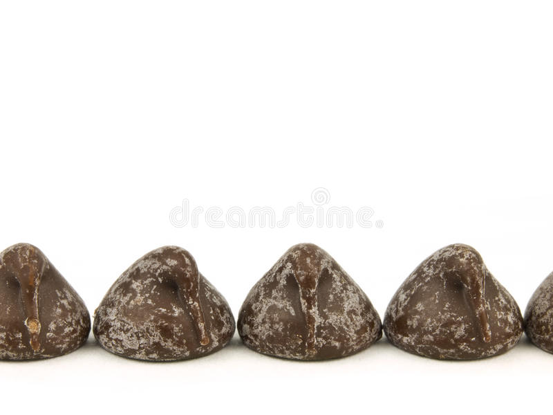 Schokoladenchips auf weißem Hintergrund stockfotos