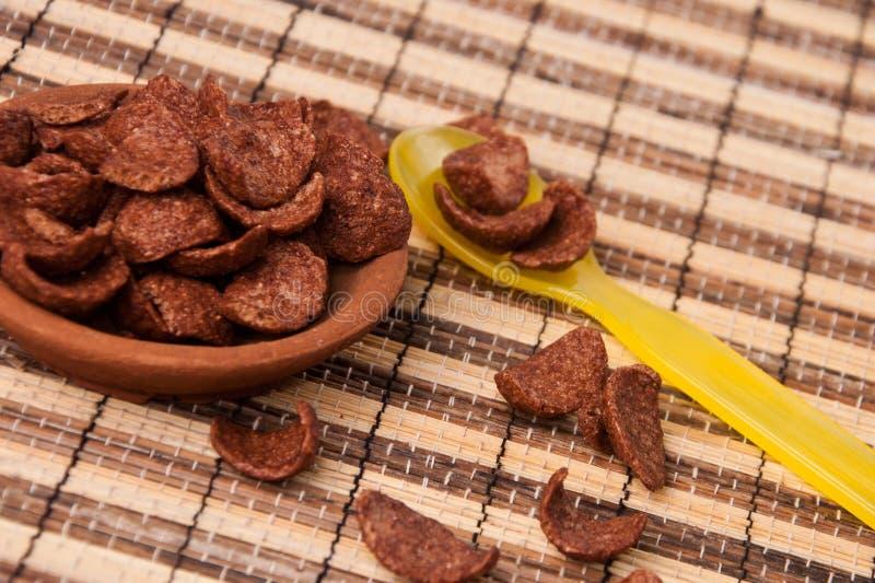 SchokoladenCorn Flakes in der Lehmscheibe und im gelben Plastiklöffel stockfoto