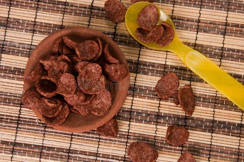 SchokoladenCorn Flakes in der Lehmscheibe und im gelben Plastiklöffel lizenzfreies stockfoto
