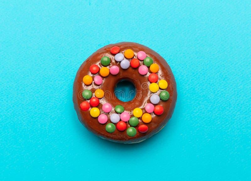 Schokoladendonut mit bunter Dekoration auf blauem Farbhintergrund, Draufsicht lizenzfreie stockfotos