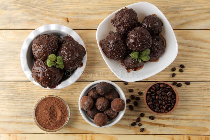 SchokoladenEiscreme mit flüssigem Schokoladen- und Kakaopulver auf einem natürlichen hölzernen Hintergrund Beschneidungspfad eing lizenzfreie stockbilder