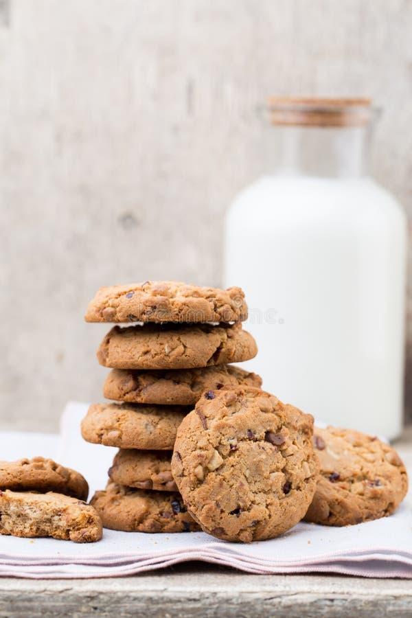 Schokoladenhafermehl-Chipplätzchen mit Milch auf dem rustikalen Holztisch lizenzfreie stockfotografie