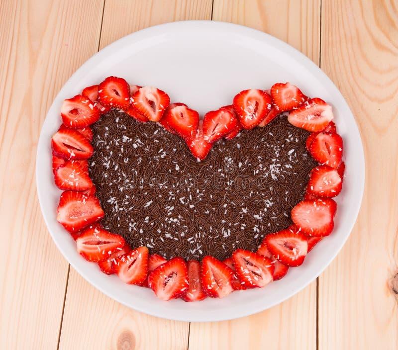 Schokoladenherz in Erdbeerrahmen stockfoto