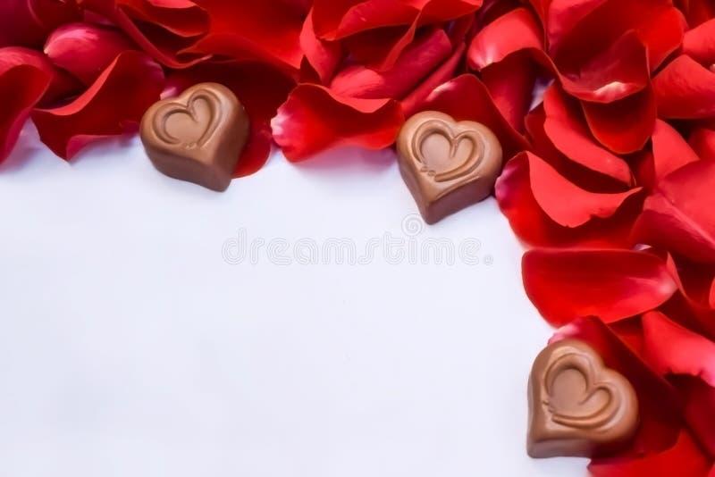 Schokoladenherzen und rote rosafarbene Blumenblätter lizenzfreie stockfotografie