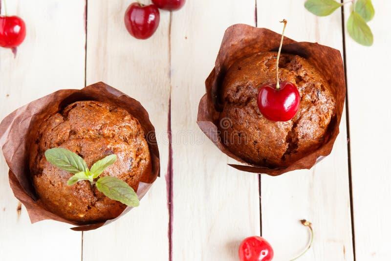 Schokoladenkleine kuchen mit Kirschen und Minze Hölzerner Hintergrund Frühstück lizenzfreies stockfoto