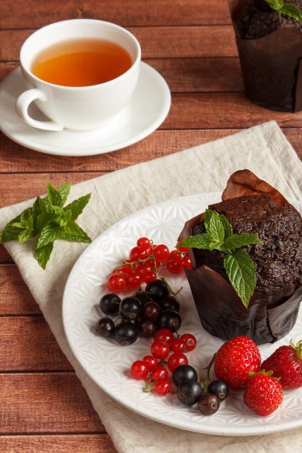 Schokoladenkleine kuchen mit Sommerbeeren lizenzfreie stockbilder