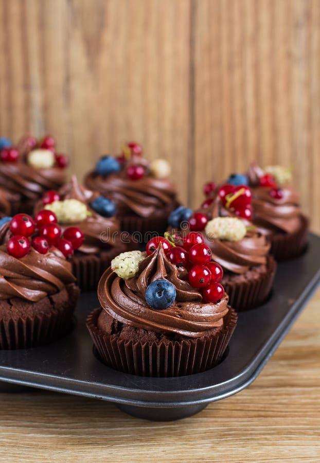 Schokoladenkleine kuchen verziert mit Schokoladencreme und Sommerbrustbeeren lizenzfreie stockfotos