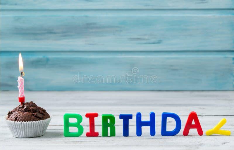 Schokoladenkleiner kuchen mit der Kerze und Geburtstag geschrieben von den Magnetbuchstaben auf hölzernen Hintergrund lizenzfreies stockfoto