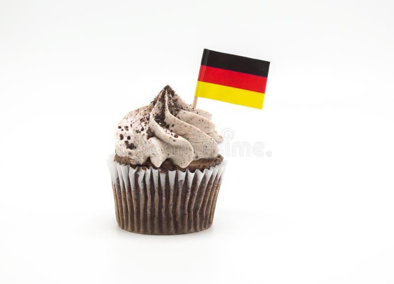 Schokoladenkleiner kuchen mit einem dreifarbigen deutschen Flaggenzahnstocher in ihm lokalisierte auf Weiß stockbild