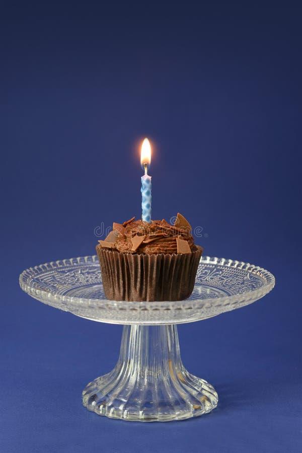 Schokoladenkleiner kuchen mit einer brennenden Kerze auf einer Glasschüssel, blauer Hintergrund mit Kopienraum, Geburtstagskonzep stockbild