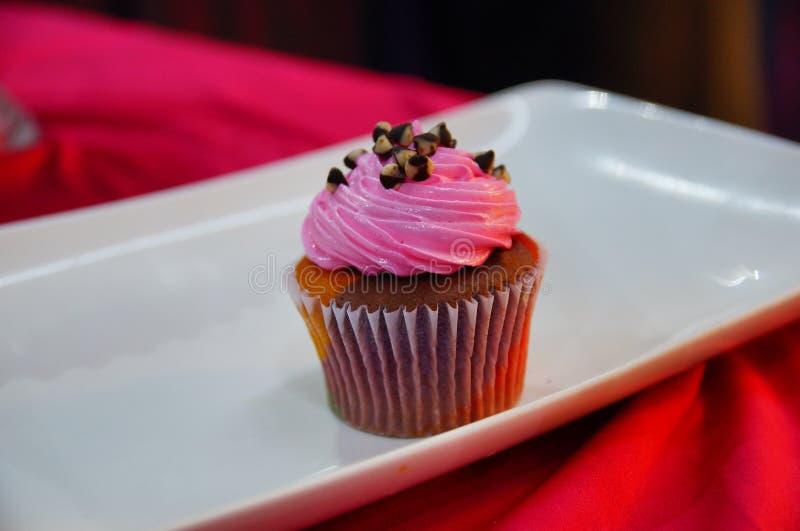 Schokoladenkleiner kuchen mit rosa Zuckerglasur stockbild