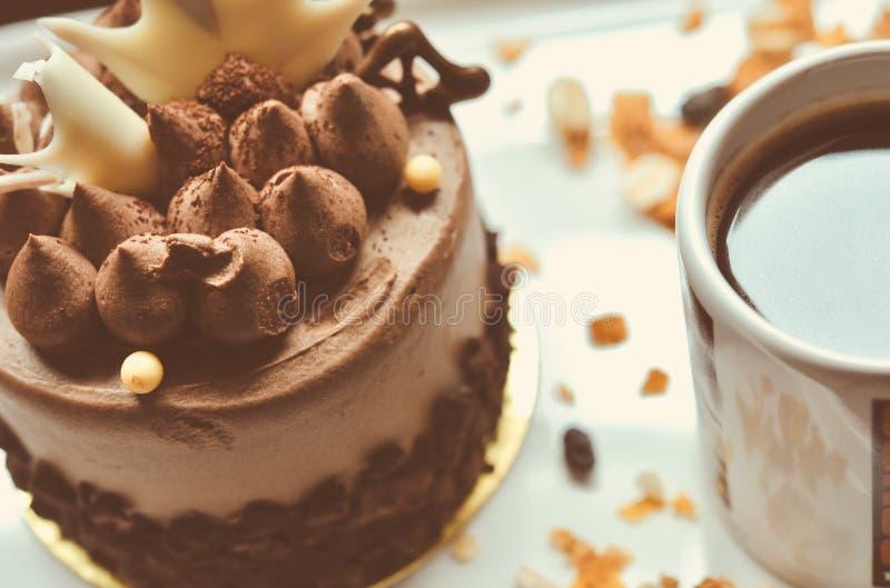 Schokoladenkuchen auf der weißen Platte mit einem Tasse Kaffee stockbild