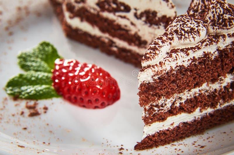 Schokoladenkuchen auf einer weißen Platte mit Erdbeeren und Minze stockfotos