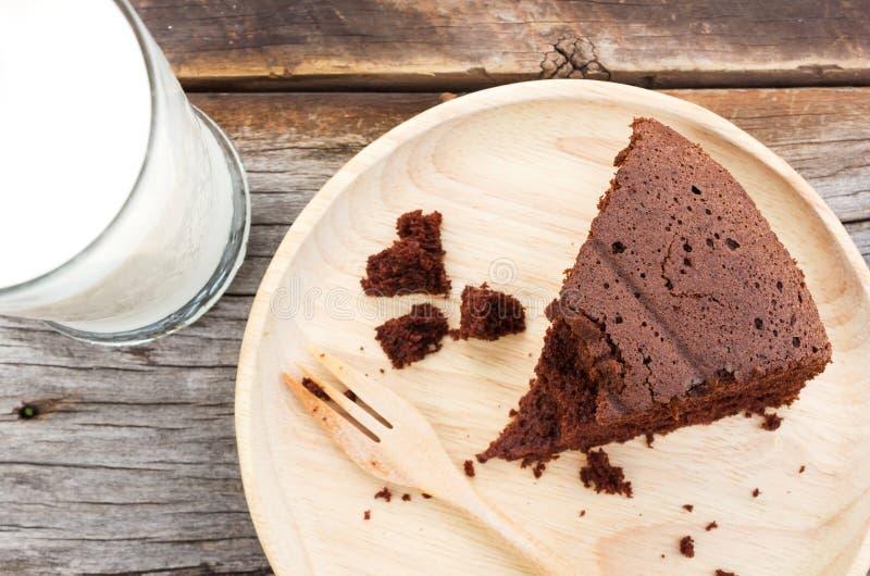 Schokoladenkuchen auf hölzerner Platte mit einem Glas Milch stockfoto