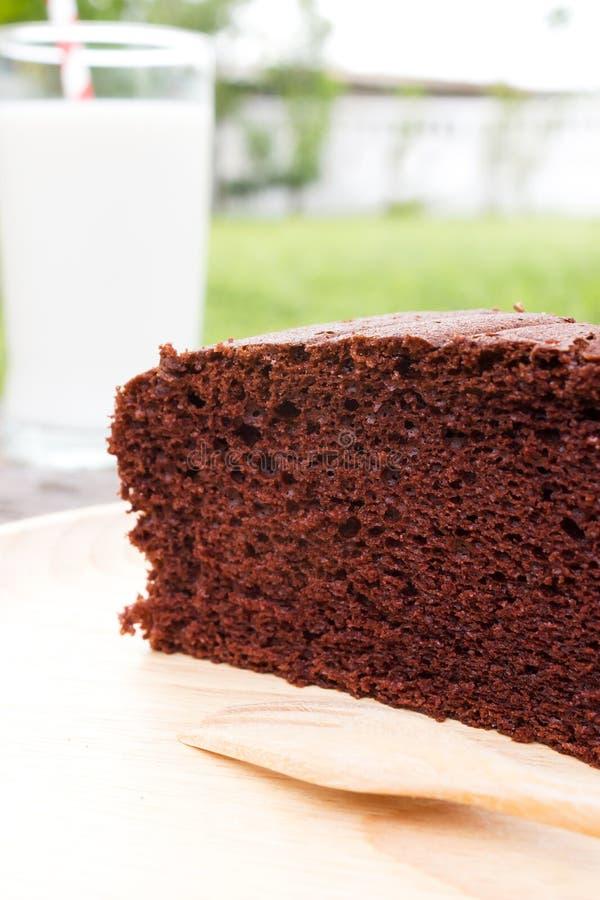 Schokoladenkuchen auf hölzerner Platte mit einem Glas Milch stockfotos