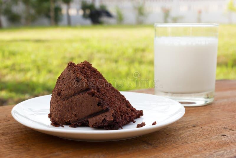 Schokoladenkuchen auf weißer Platte und einem Glas Milch stockfoto